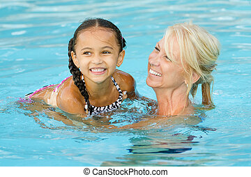 Mother and mixed race girl in pool - Mother and mixed race...
