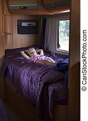 Child in camping caravan - A girl sleeping in a bunk bed...