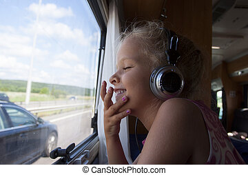 child travelling in a camping caravan - A happy girl with...