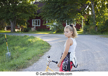 Child on bicycle on country road - An alone girl looking...