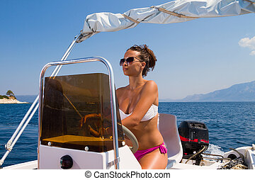 young woman driving a speedboat - A stunningly beautiful...