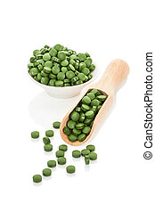 Green pills. - Green pills in bowl and on wooden scoop....