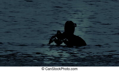 Navy Seals Diver in the night, moonlight reflection on the...