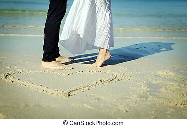 Couple on the beach with symbol of heart on the sand