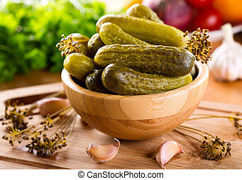 Salted cucumbers in a bowl on wooden table