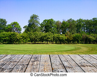 Empty wooden floor against green forest with meadow