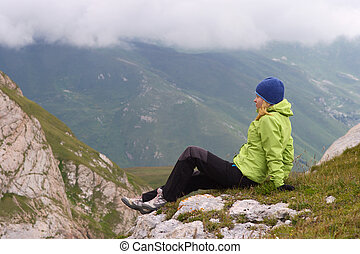 Woman Hiker in Mountains relaxing sitting on rocky cliff with clouds on background