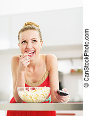 Smiling young woman eating popcorn and watching tv in kitchen