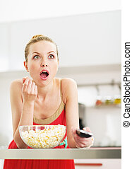 Surprised young woman eating popcorn and watching tv in kitchen