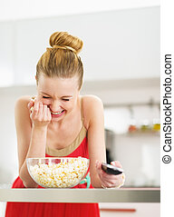 Laughing young woman eating popcorn and watching tv in kitchen
