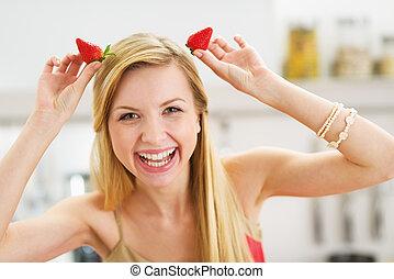 sonriente, joven, mujer, Elaboración, cuernos, fresas