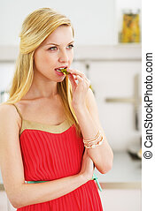Thoughtful young woman having snack in kitchen