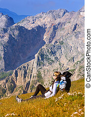 Woman Hiker in Mountains relaxing on grass with backpack rock peak on background
