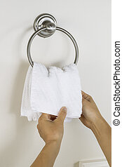 Female hands putting clean wash cloth on Towel Ring Holder -...