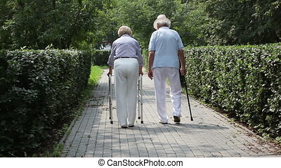 Retired couple - Senior woman using a walker accompanied by...