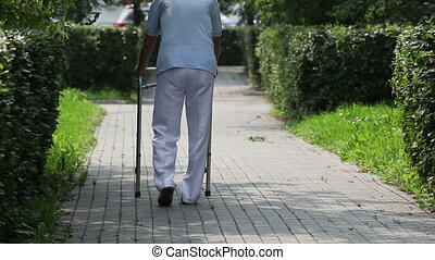 With effort - Back-view of an elderly nursing-home patient...