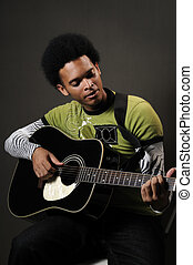 Man playing guitar - Portrait of young african american man...