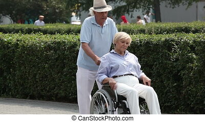 Wheelchair walk - Retired man taking his disabled wife for a...