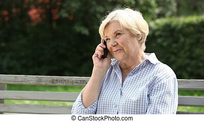 Modern retiree - Modern retired woman making a call and...