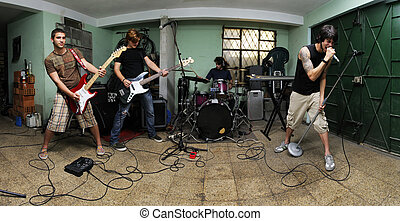 Rock band on garage - Group of young male musicians playing...