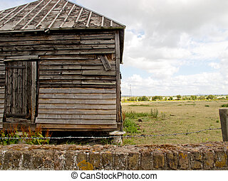 An old shack in a field - An image showing an old shack with...