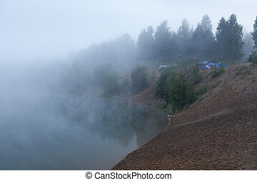 Fog on the lake with standing tourist tents at early morning