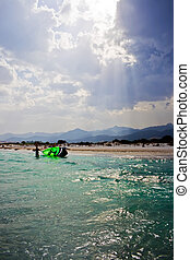 Kite surfer - a kite surfer near la Cinta beach in Sardinia,...
