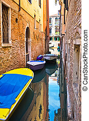 Canal in Venice - narrow canal with boats in Venice, Italy