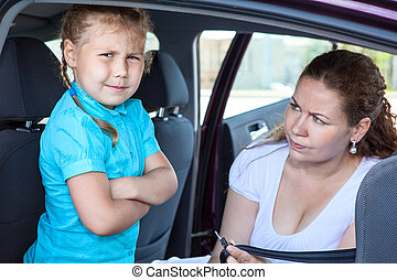 Mother convincing a girl to get in child safety seat against...