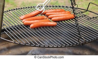 grilling hotdogs on a campfire - grilling hotdogs over a...