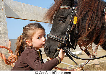 little girl and her pony - little girl kissing and her...