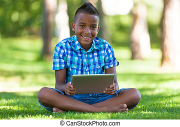 Outdoor portrait of student black boy using a tactile tablet...
