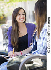 Attractive Expressive Young Mixed Race Female Student Sitting and Talking with Girlfriend Outside on Bench.