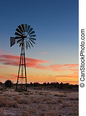 Kalahati sunset with trees grass windmill and blue sky