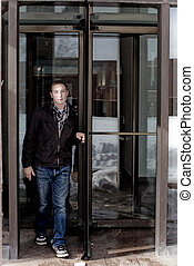 Revolving Rotating Door - Man in his twenties walks through...