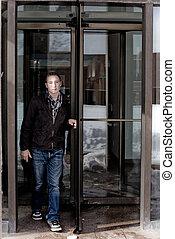 Revolving Rotating Door - Man in his twenties walks through...