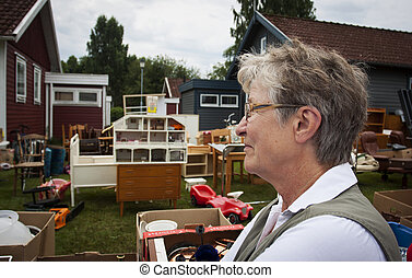 Senior woman at auction - An old woman at a yard sale