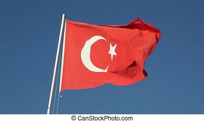 Turkish flag waving in wind against clear blue sky