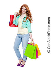 smiling young redhead girl with colorful shoppingbags...