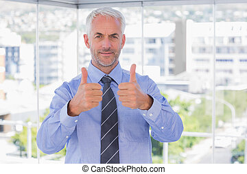 Businessman smiling with his thumbs