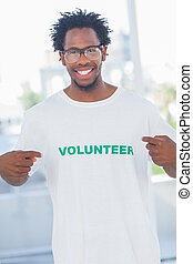 Cheerful man pointing to his volunteer tshirt in a modern...