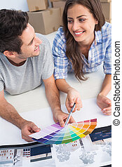 Happy couple looking at a color chart to decorate their...