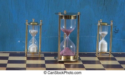 three sandglass on chessboard. Time concept