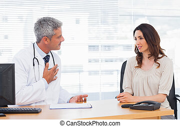 Serious patient talking with her doctor about illness in...