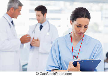 Nurse writing on a clipboard while doctors are talking...