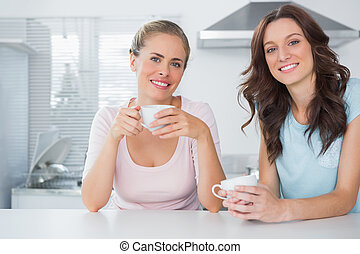 Cheerful friends having cup of coffee in the kitchen