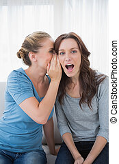 Astonished woman being told a secret by her friend and...