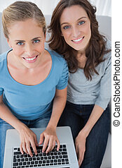 Women posing while surfing the net and sitting on the sofa