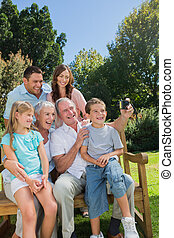 Multi generation family sitting on a bench taking photo of...