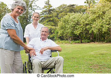 Cheerful man in a wheelchair with his nurse and wife